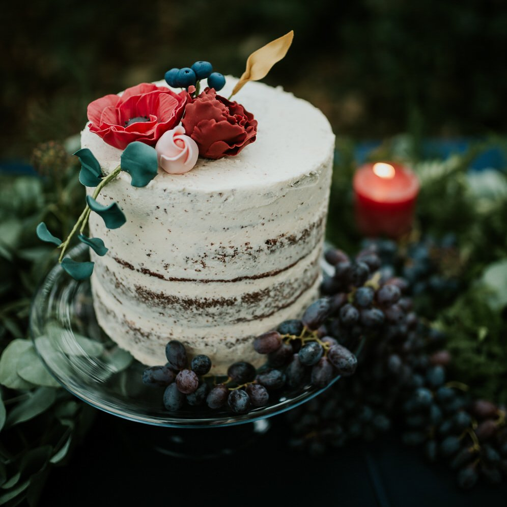 small wedding - cakea close up image of a small wedding cake covered in wild berries and edible flowers