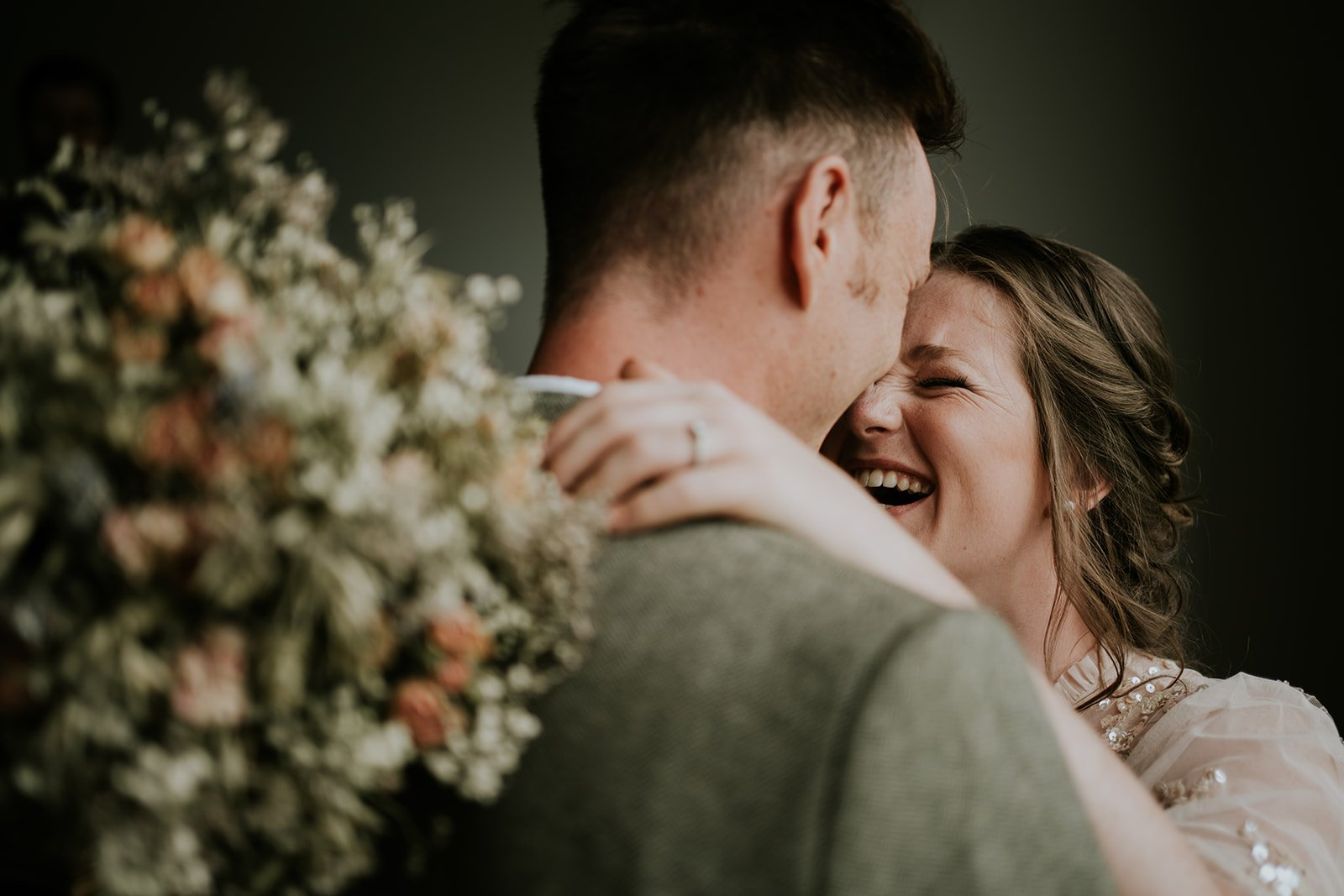 a close up shot of a brides head close to grooms she laughs with her arms around his head