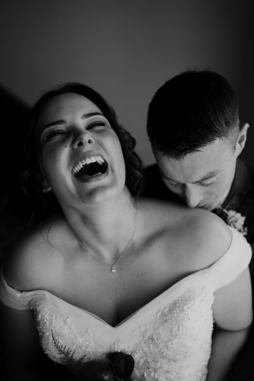 Bride laughs with her head thrown back and her mouth open as the groom kisses her on the shoulder