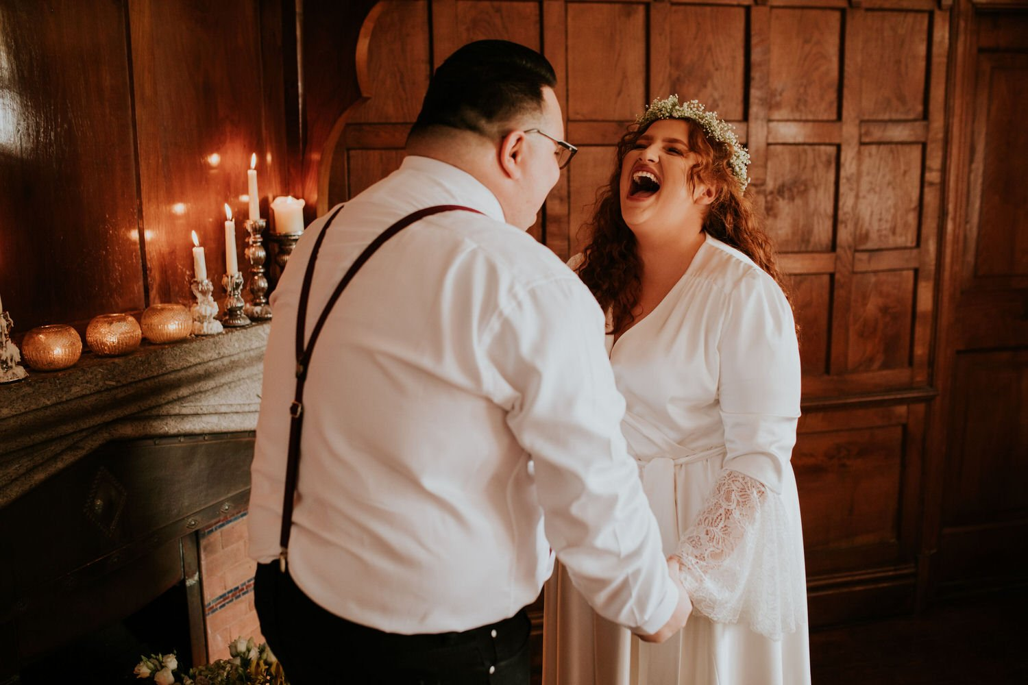 Bride throws her head back and laughs during the vows of her elopement at BoHo Cornwall