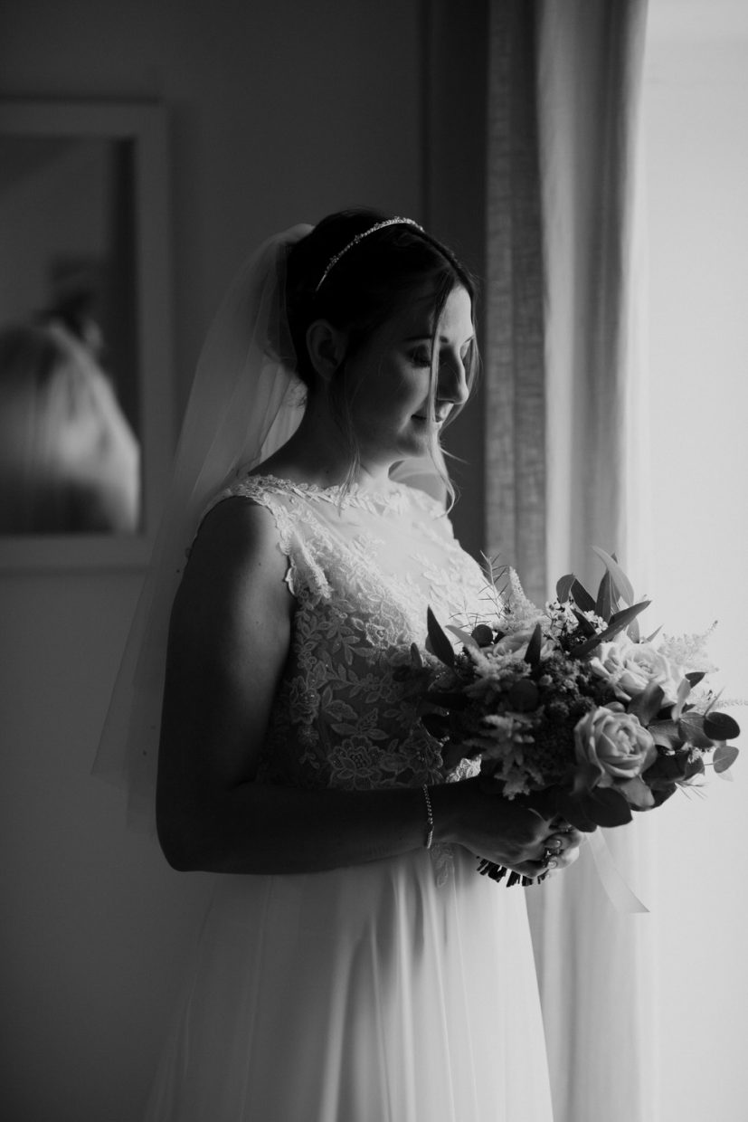 A bride stands in the window gazing out waiting for her ceremony whilst holding her bouquet