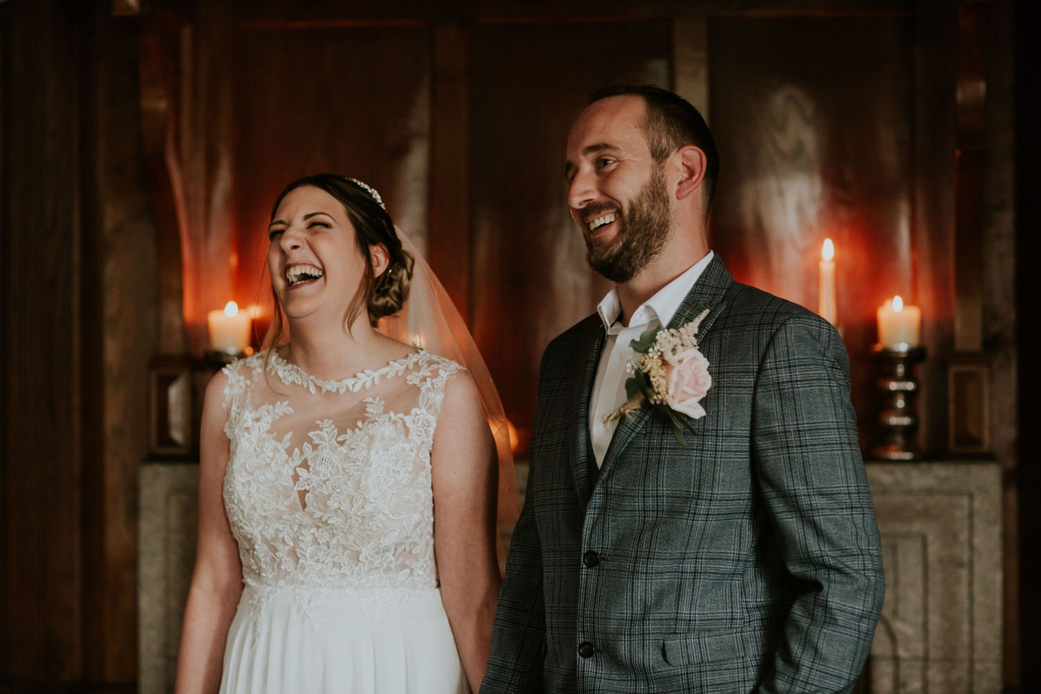 Bride laughs during her elopement with her groom in a candlelit ceremony in Cornwall