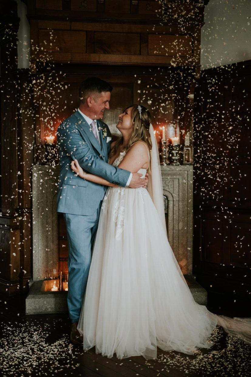bride and groom embrace passionately and stare into each others eyes as confetti is thrown on them