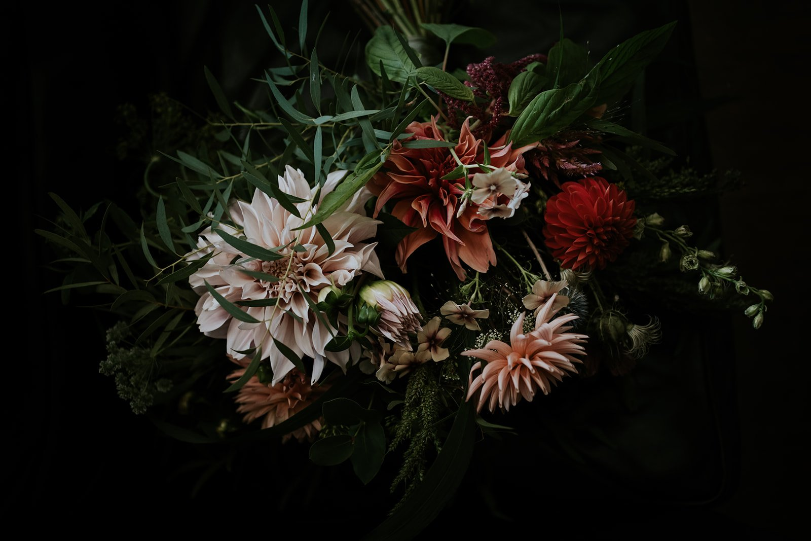 a close up image of a seasonal wild bouquet with lots of reds and pinks and greens
