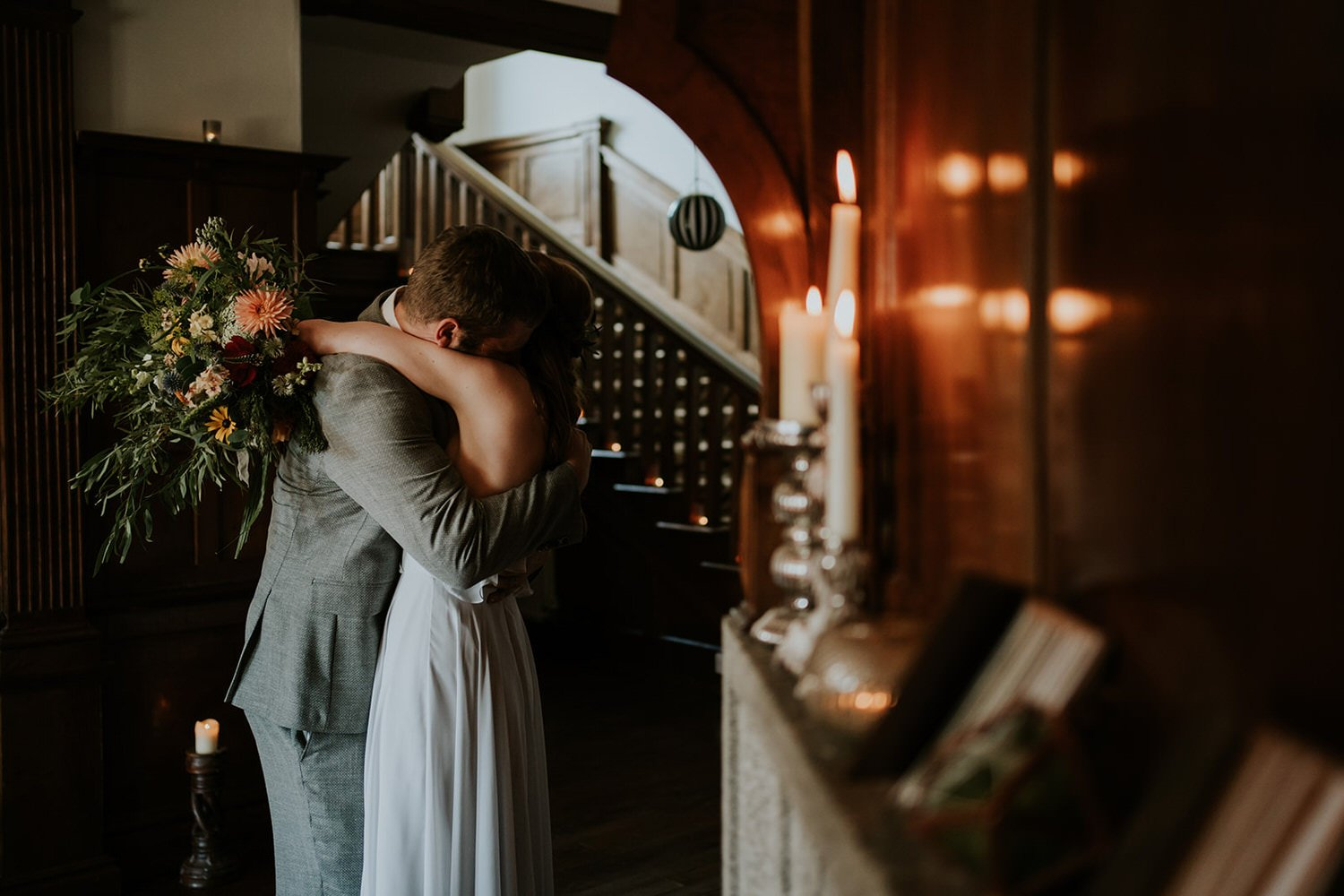 Couples hug tightly after their intimate ceremony the brides arms around the grooms neck whilst holding a huge wild bouquet