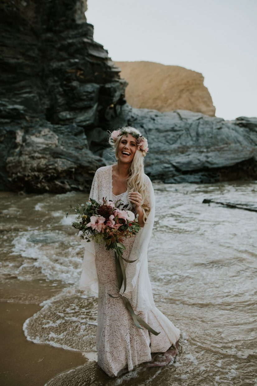 Elopement Bride holding her bouquet and laughing in the sea as the water crashes around her