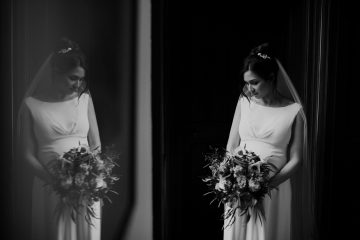 moody black and white portrait of a bride in a window holding flowers whist her reflection can be seen in a mirror