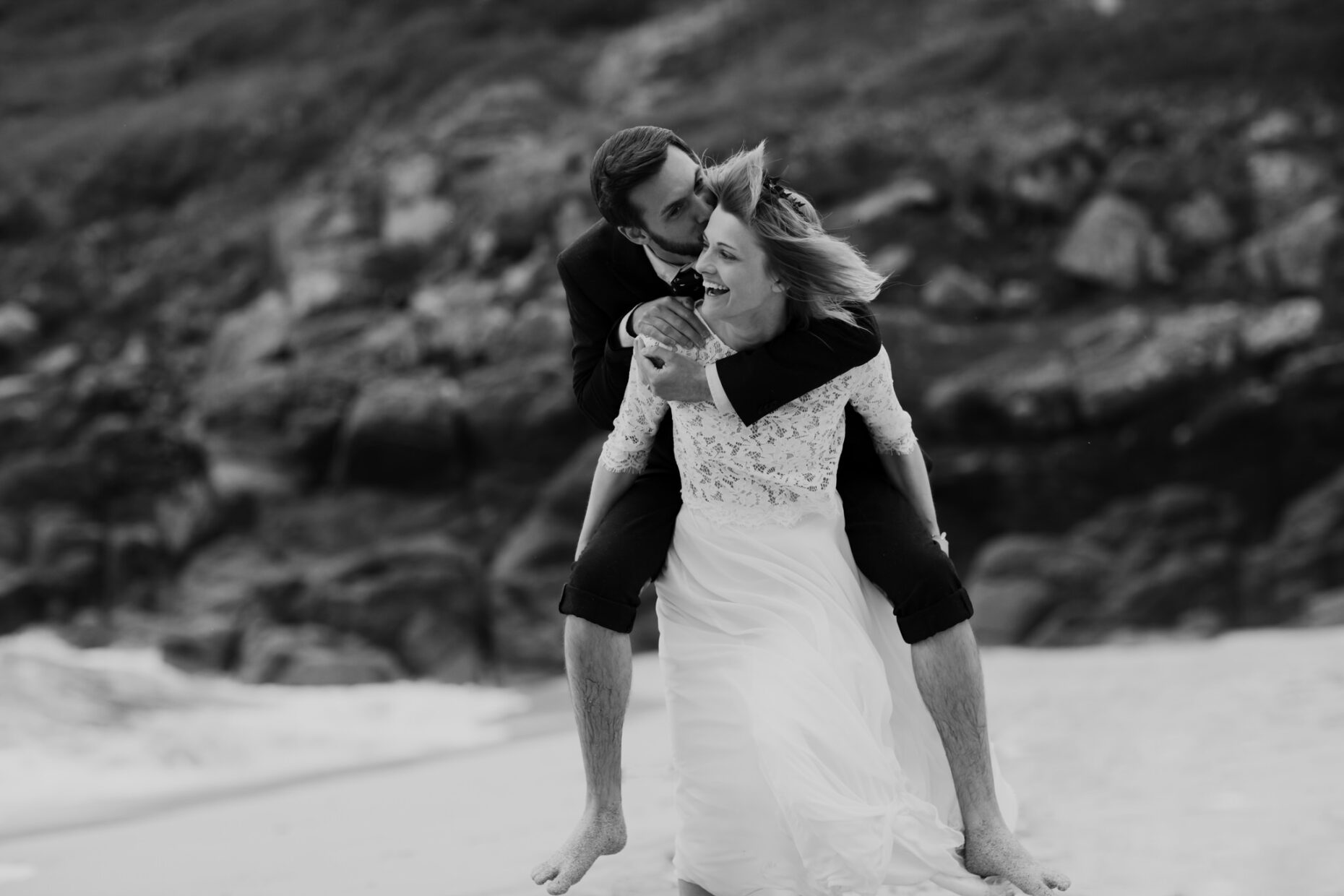 a bride piggybacks groom as they run across beach barefoot with smiles on their faces