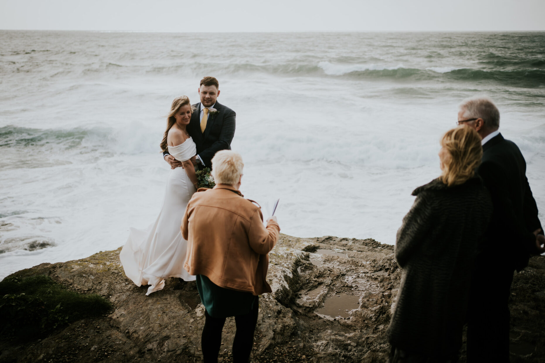 A celebrant conducts a ceremony on a dramatic cliff with a couple as the sea crashes behind them and her parents watch