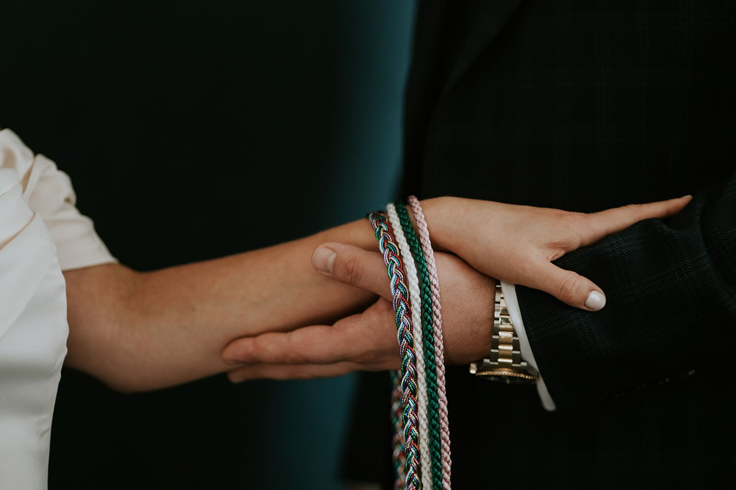 Wedding celebrant places the handfasting cords on a couples wrists during a wedding in Cornwall