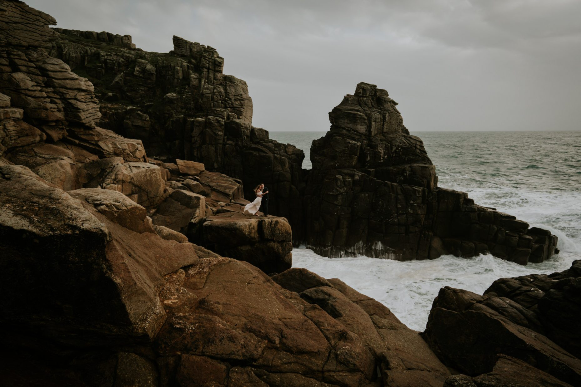Couple kiss on the cliffs as the wild cornish sea crashes behind them