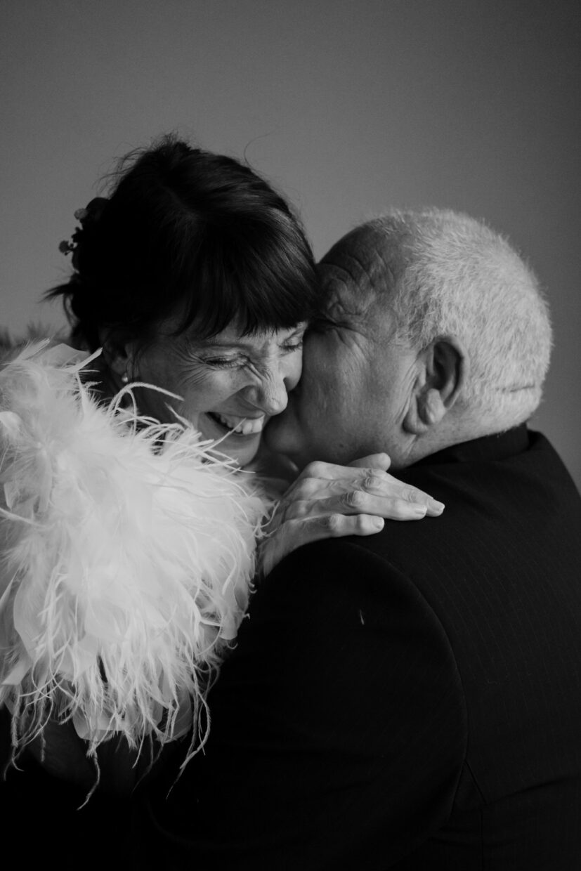 A black and white image of an older couple on their elopement, holding each other highly as the groom kisses the brides ear and she laughs