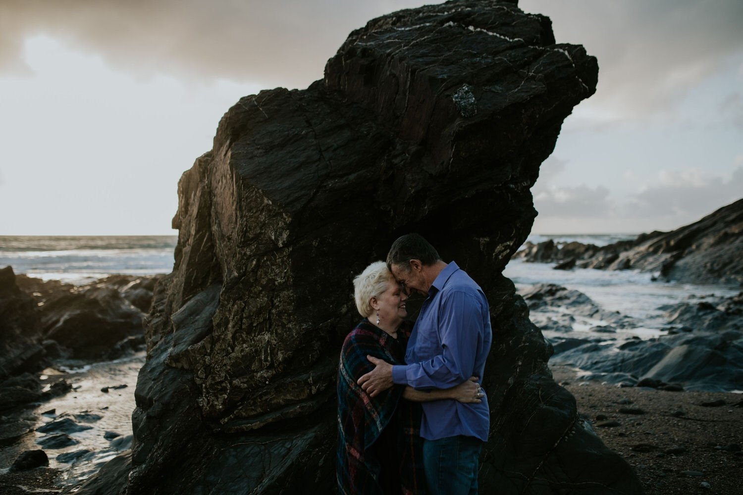 a couple stand close together, their heads touching on the edge of the sea during their outdoor ceremony in Cornwall