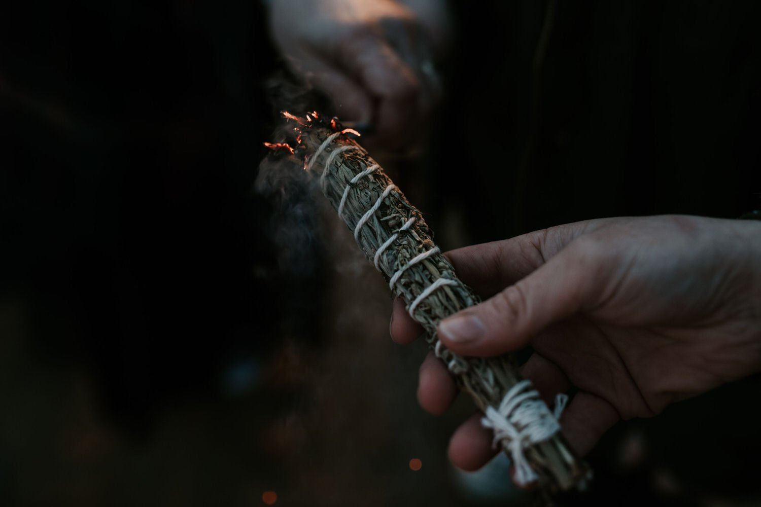 A close up detail shot of a pagan ceremony of someone burning some sage to cleanse the space