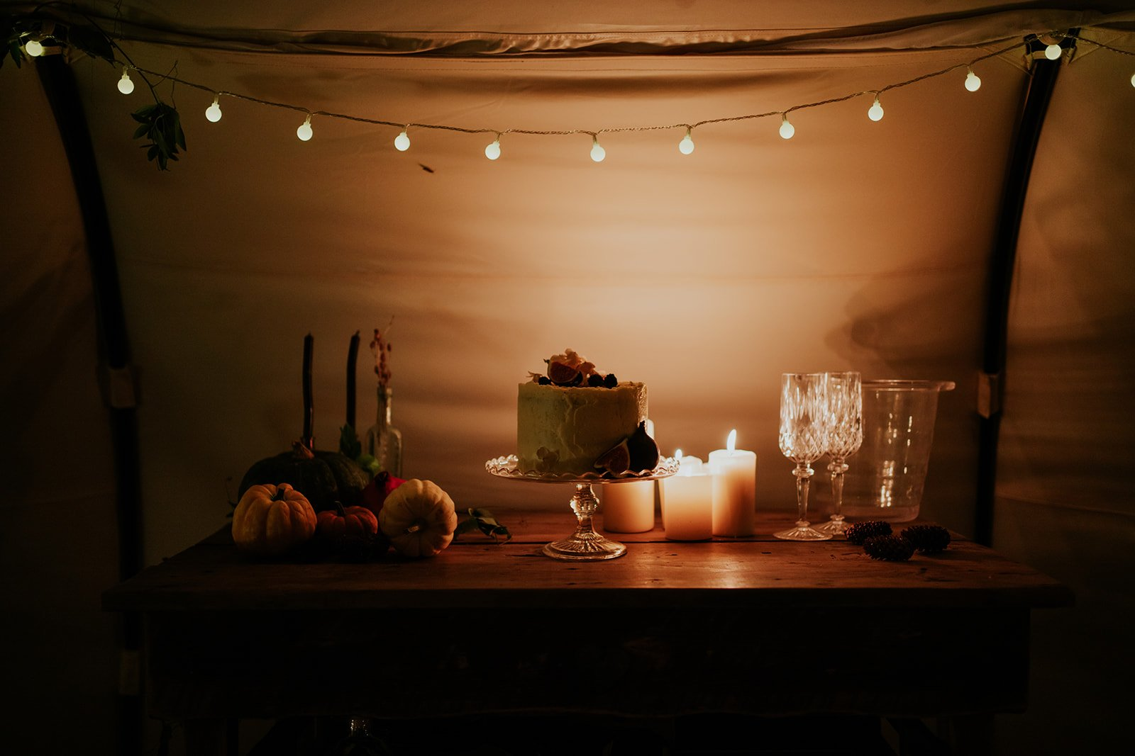 intimate wedding with candles and food in tent