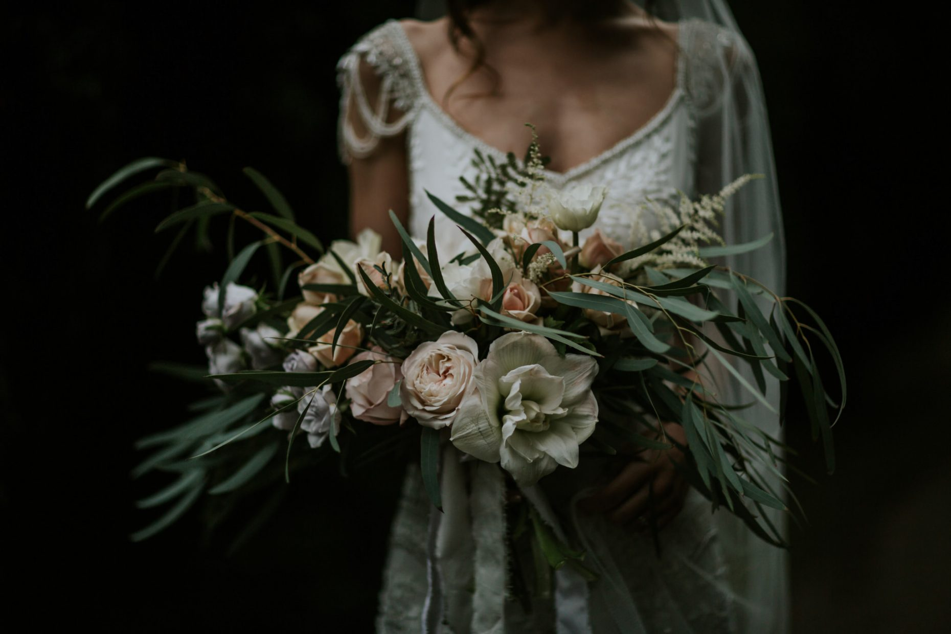 A close up shot of a bride against a dark background holding a huge bouquet of flowers