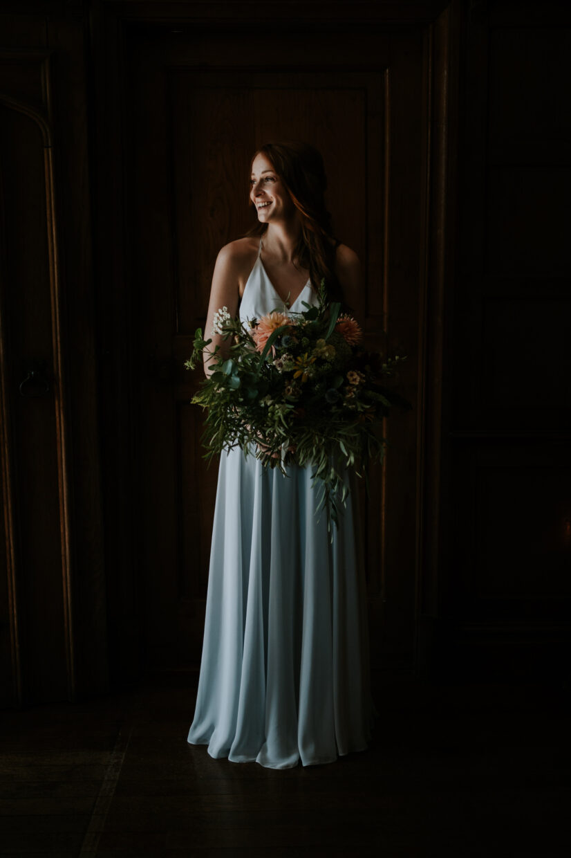 bridal portrait of a beautiful red haired bride holding a huge bunch of wild flowers and wearing a grey wedding dress looking out of the window