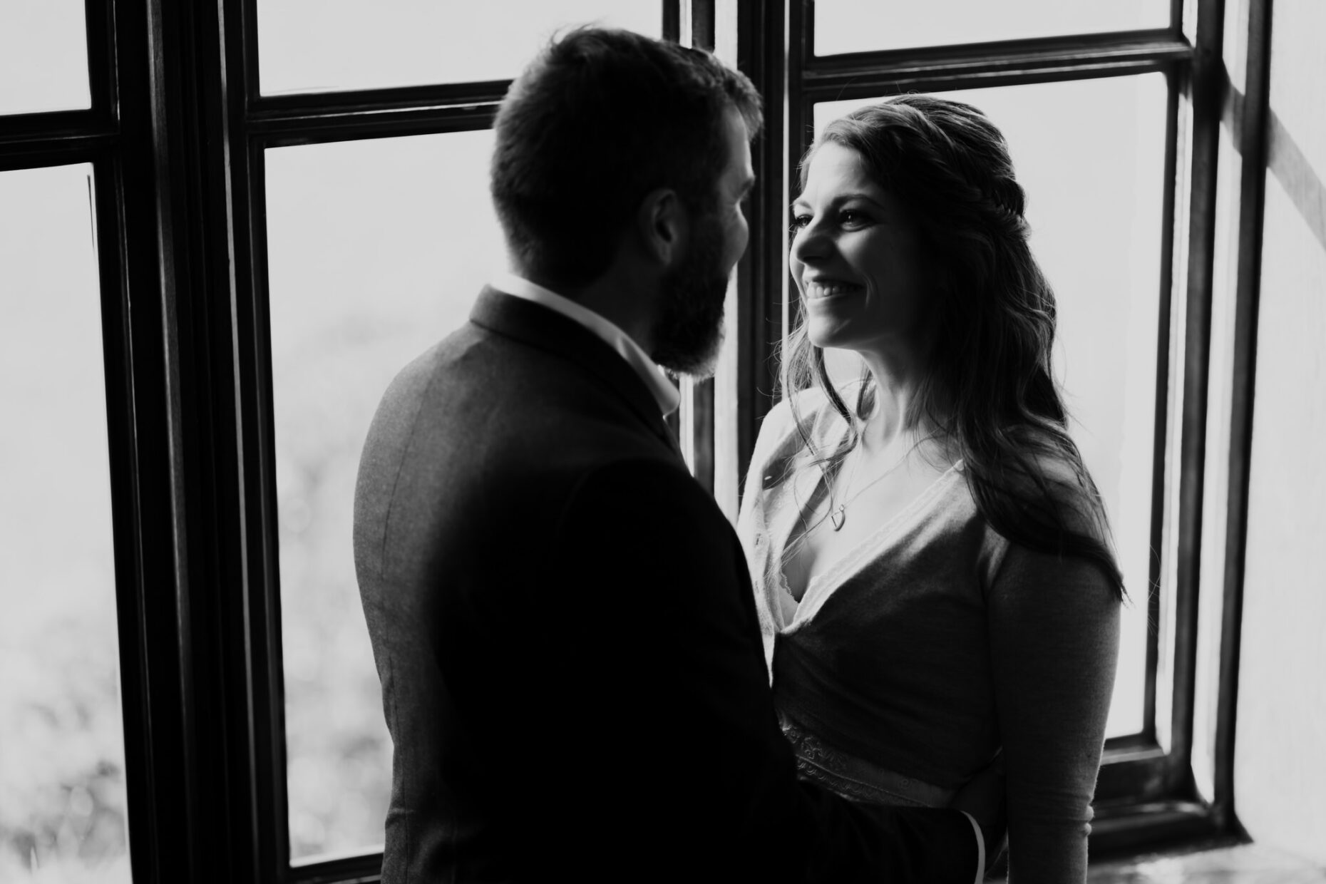 black and white image of couple in the window looking emotionally at one another