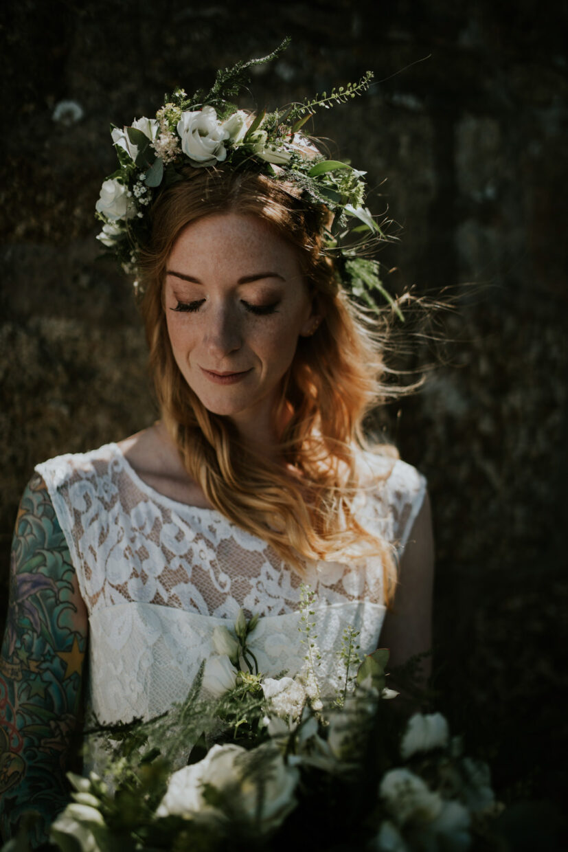 bride before her ceremony holding a bunch of wild flowers in her hands whilst she displays a big flower crown on her head