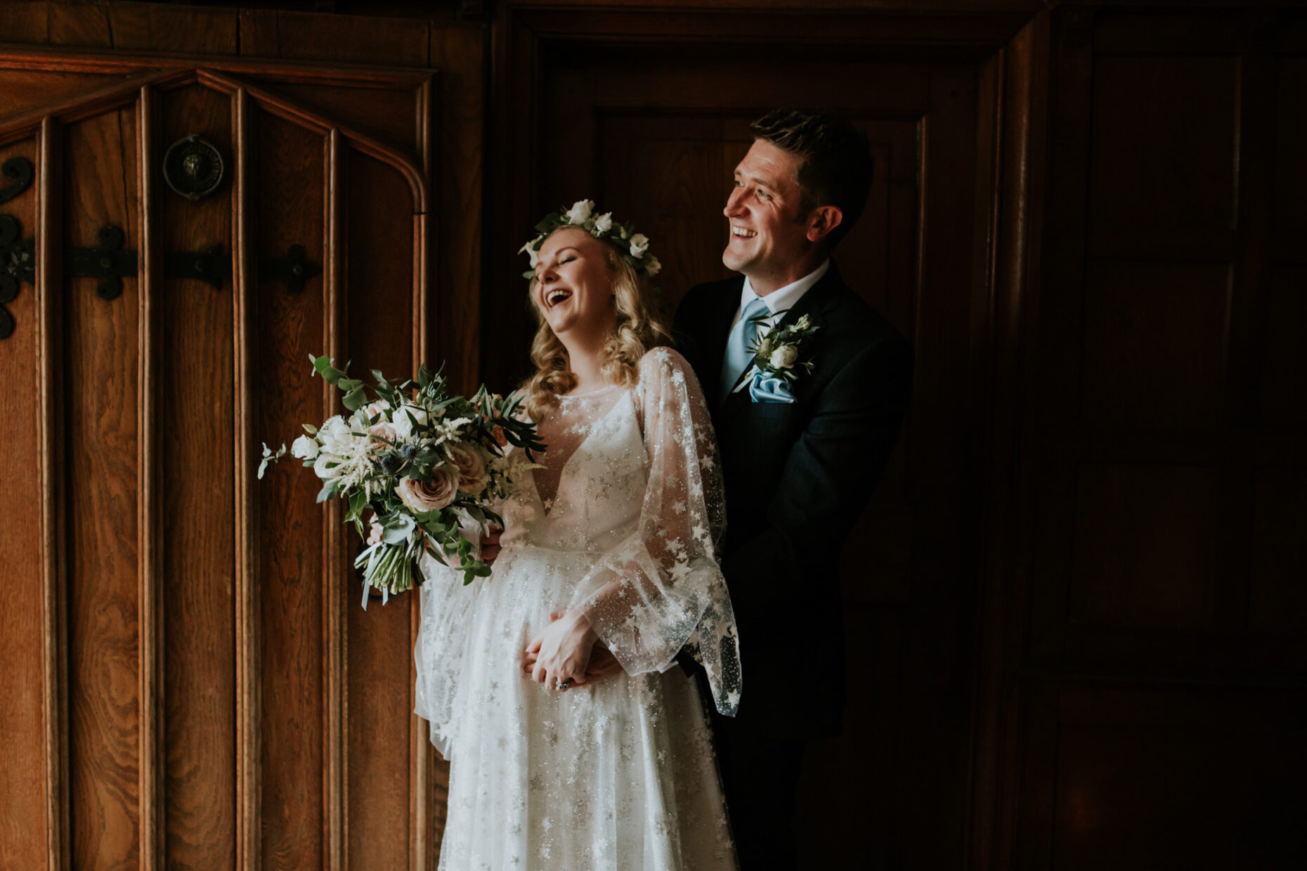 Bride and groom laughing as they cuddle in the door way with dark oak panelled walls as their backdrop