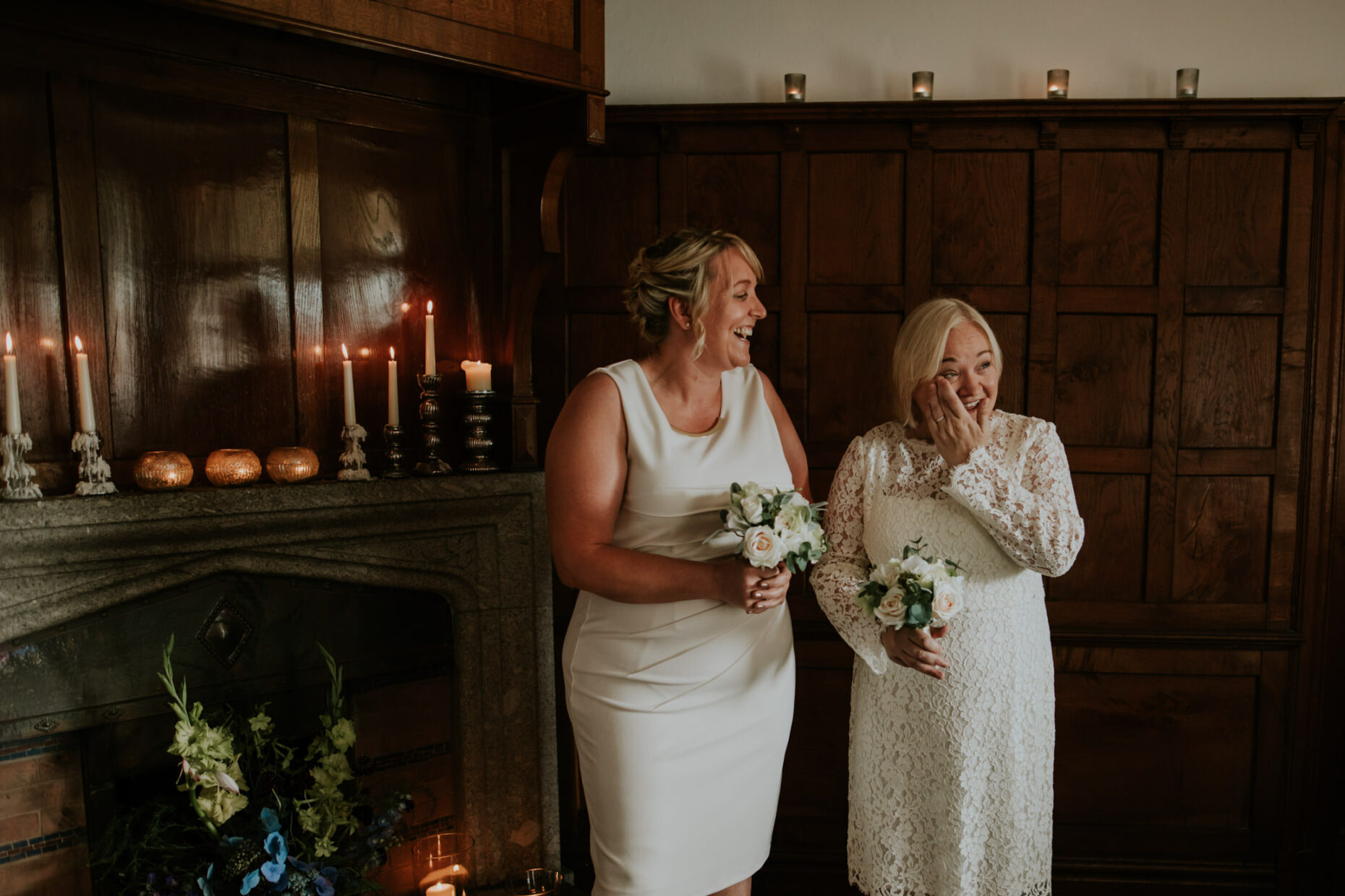two brides stand close to each other during their ceremony and one bride is wiping away a tear from her cheek