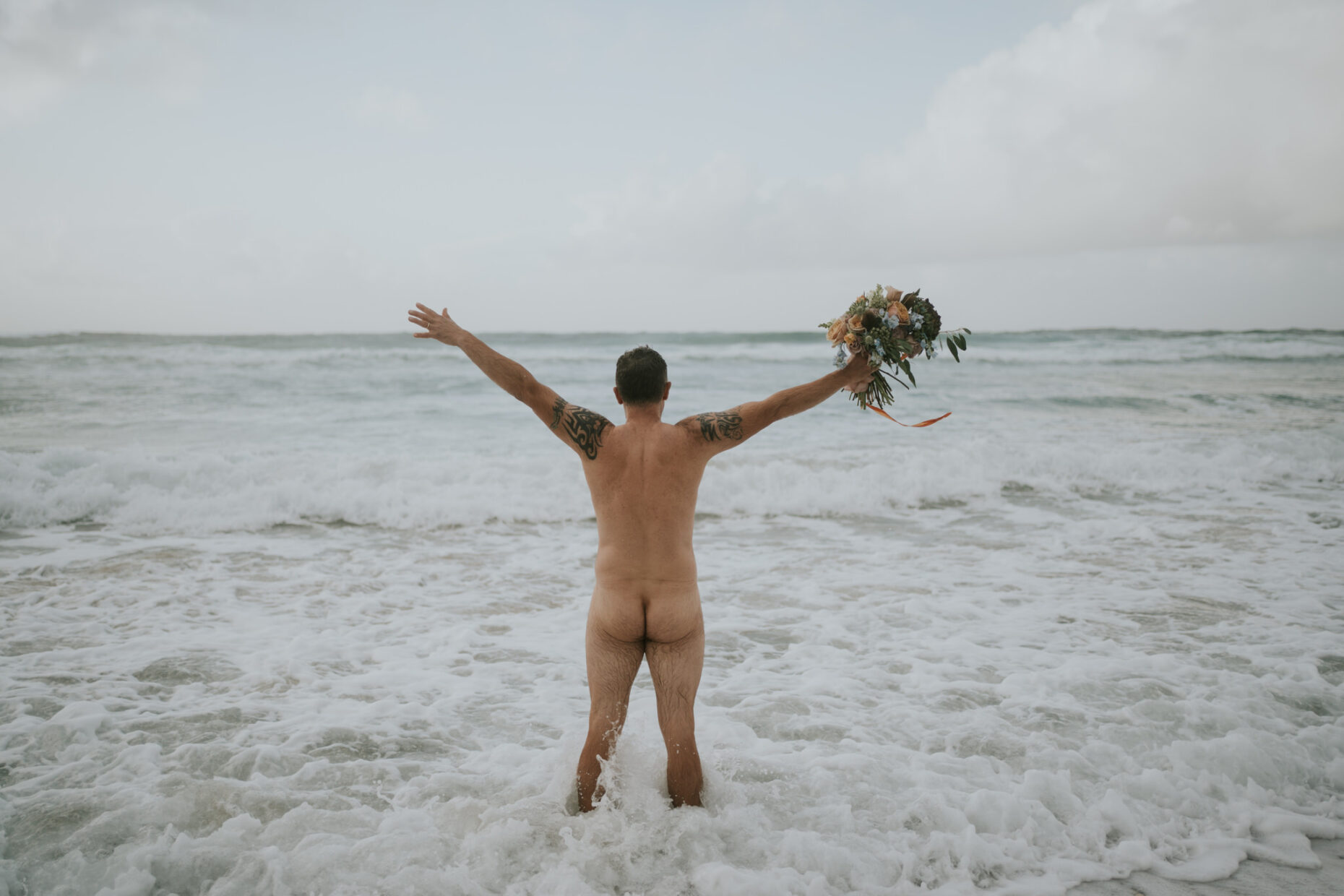groom runs naked into the sea on his wedding holding his wife's bouquet as the waves crash around him