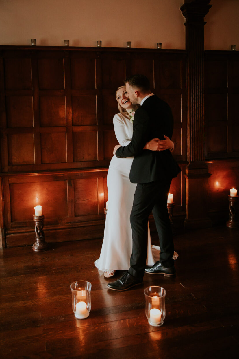 Couple hug tightly and the bride is laughing whilst the groom holds her close and kisses her on the cheek with candles around them