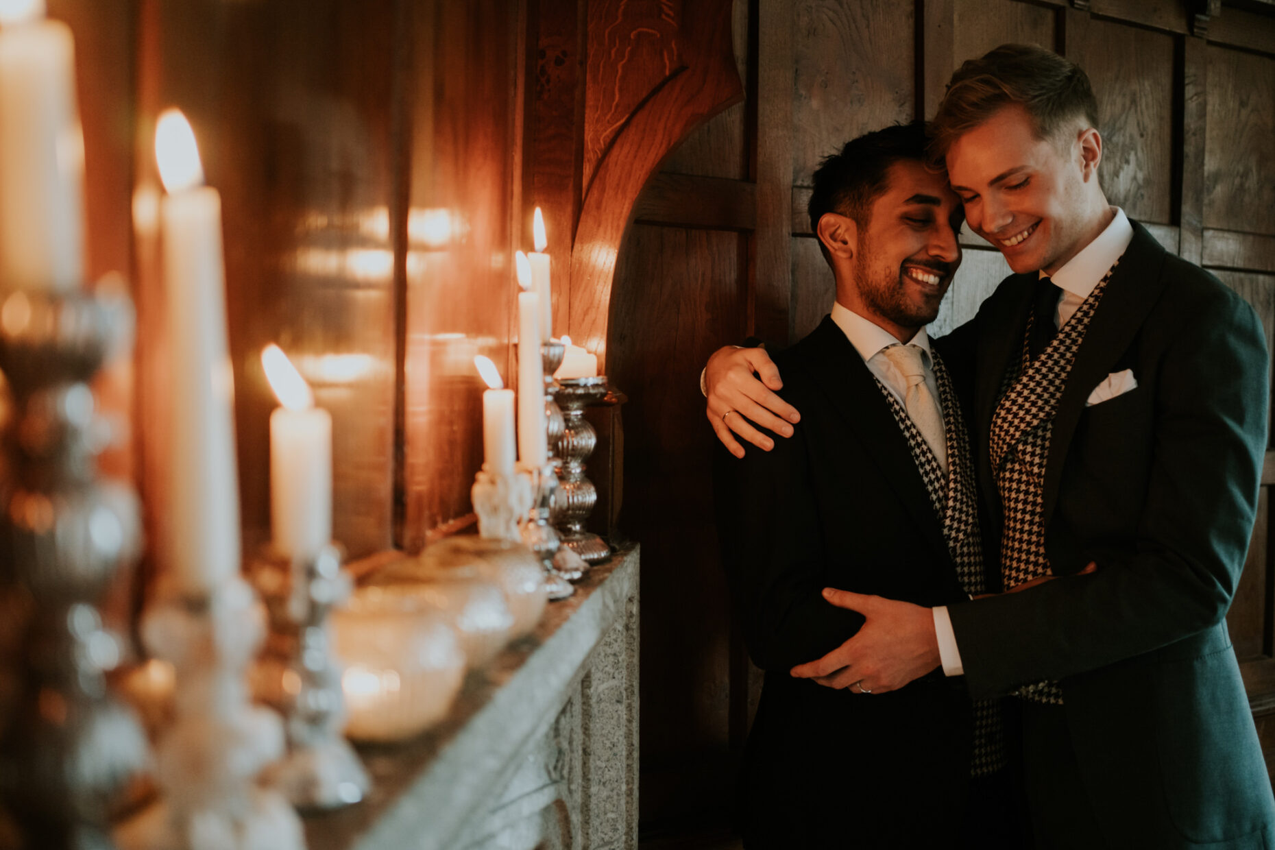two groom hug tightly next to a fireplace and the orange glow from the candles lights and warms their faces