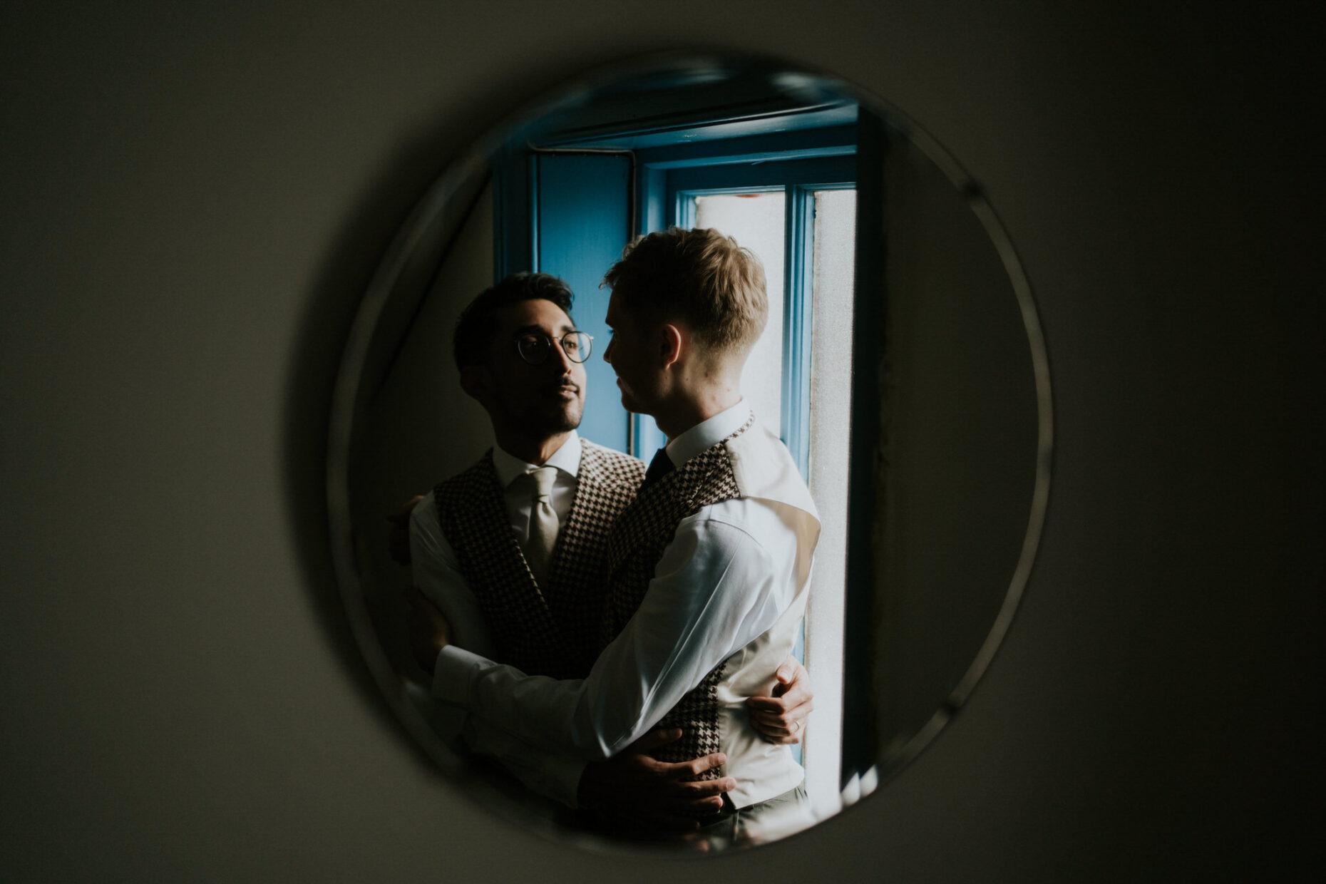 a gay couple stare lovingly into each others eyes and you can see them through a round mirror which is framing them