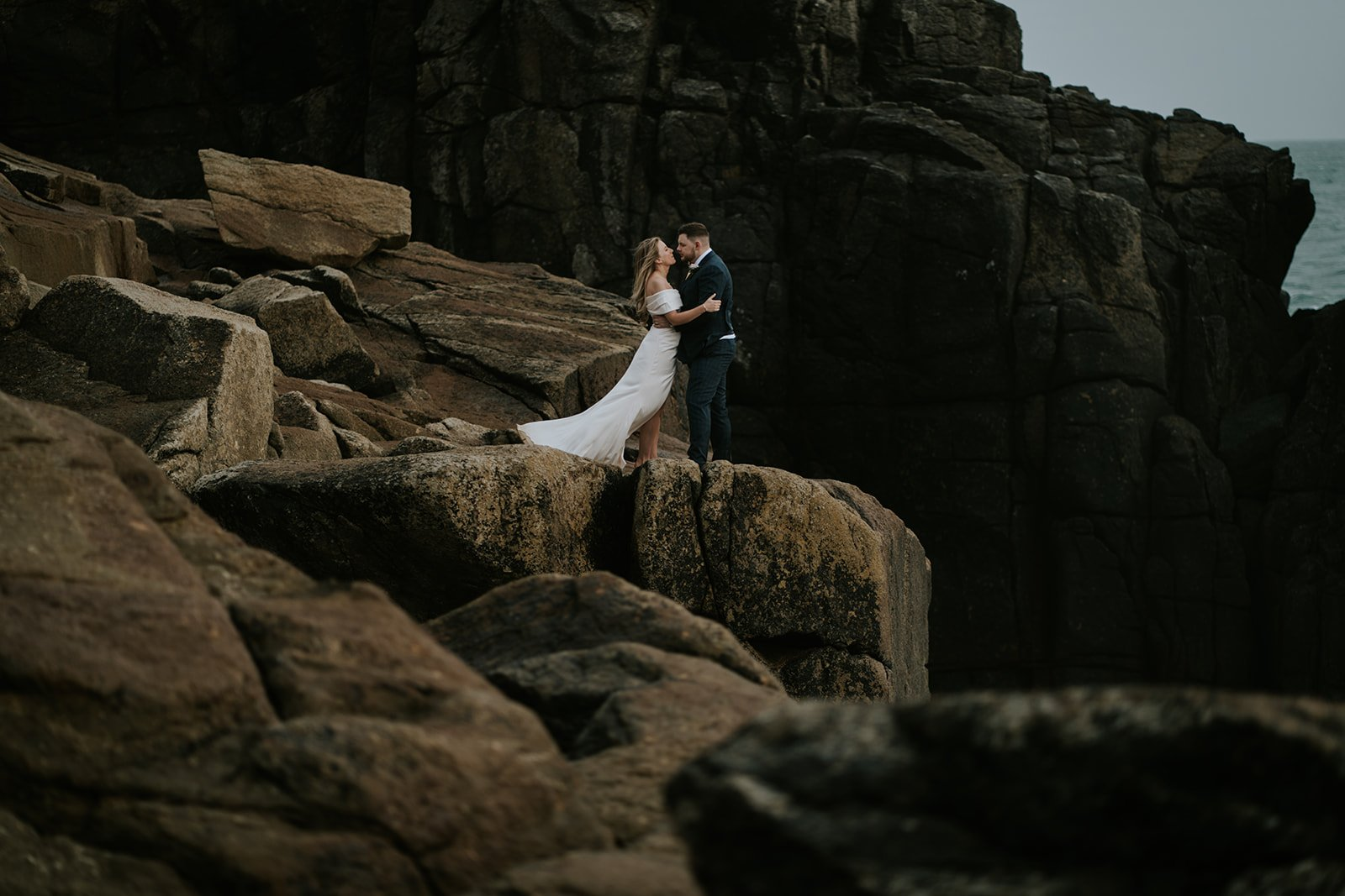 Couple kiss wildly on the rugged cliffs during a storm as huge waves crash below them