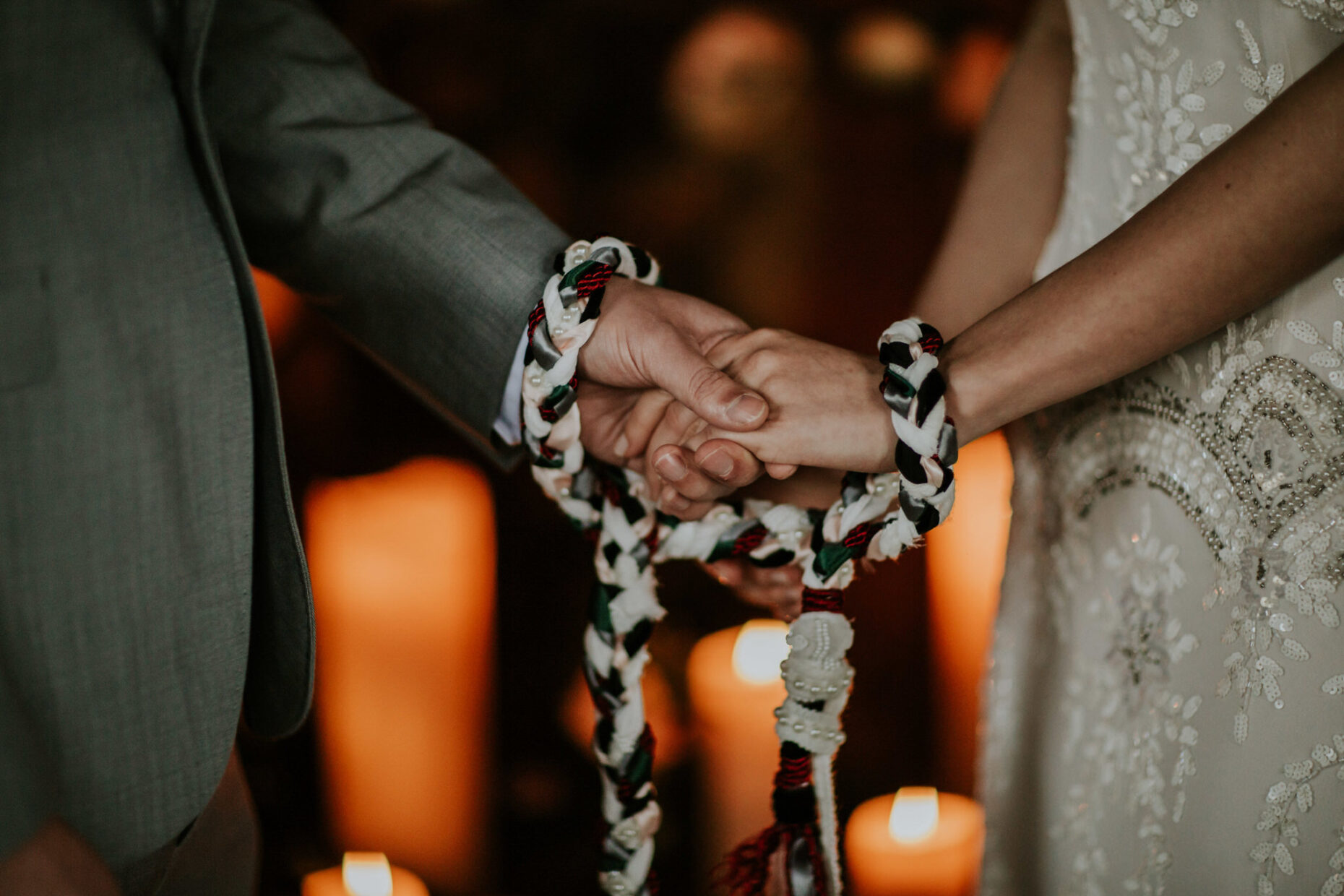 a close up image of a couple having their hands tied by a hand fasting cord during their ceremony with candles behind them