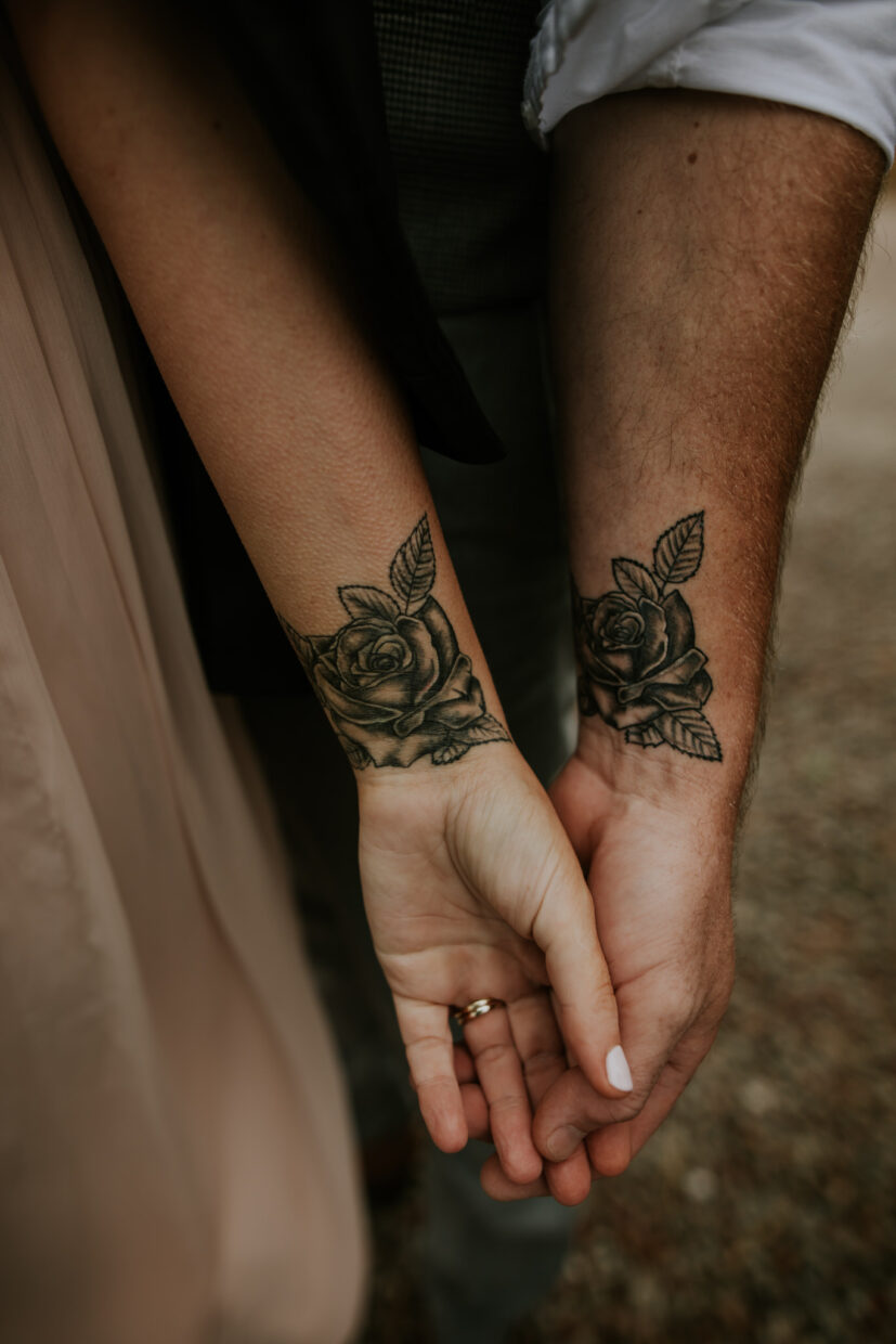 bride and groom hold hands softly and they both have matching tattoos on their writes of roses