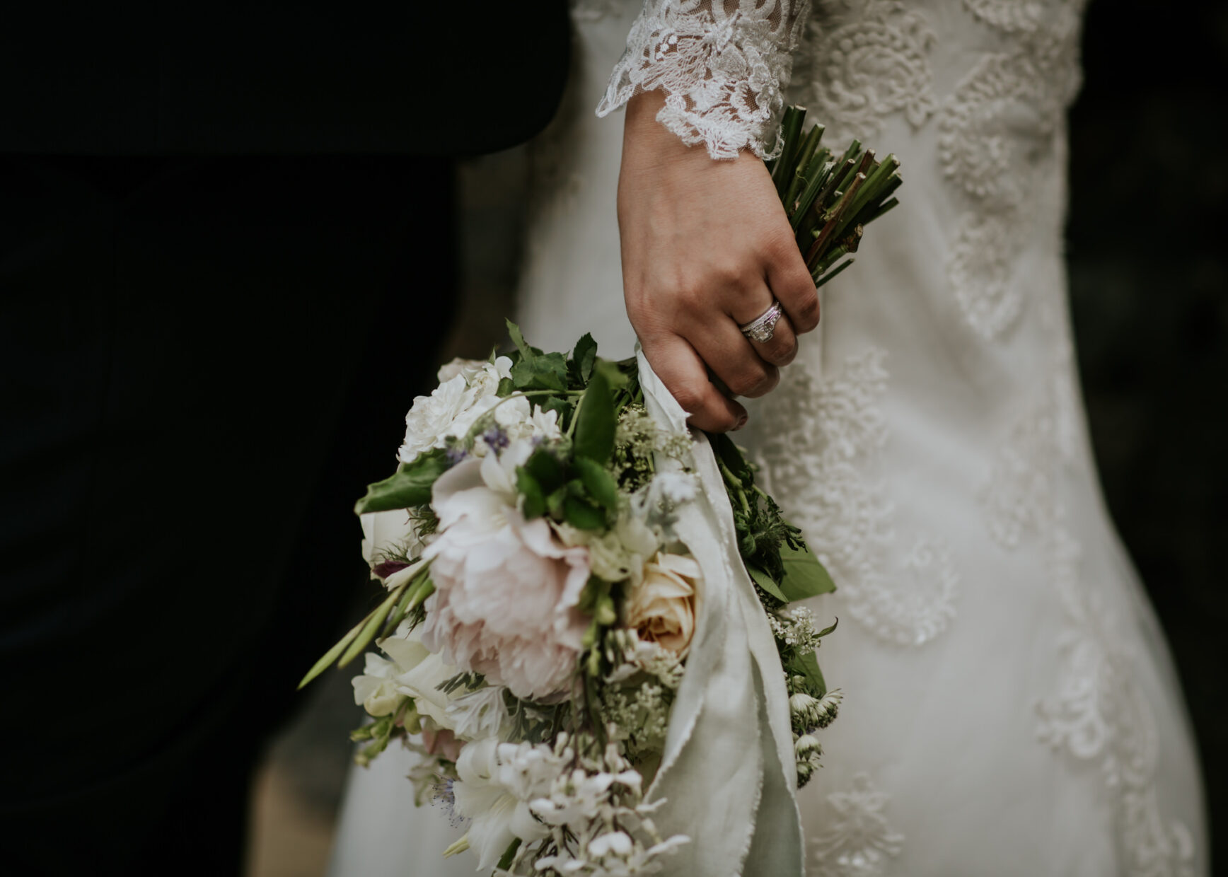Bride holds her bouquet by her side, her wedding ring on display after her ceremony with a celebrant
