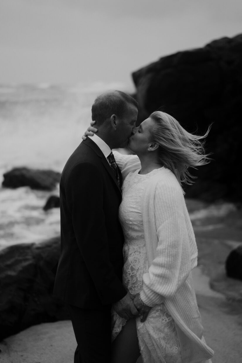 bride and groom kiss during a big storm on the beach