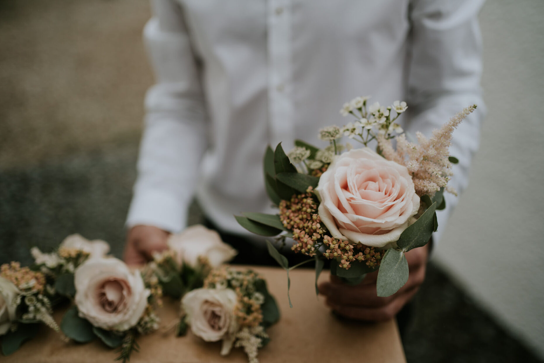 A groom passes out the buttonholes from his elopement in Cornwall