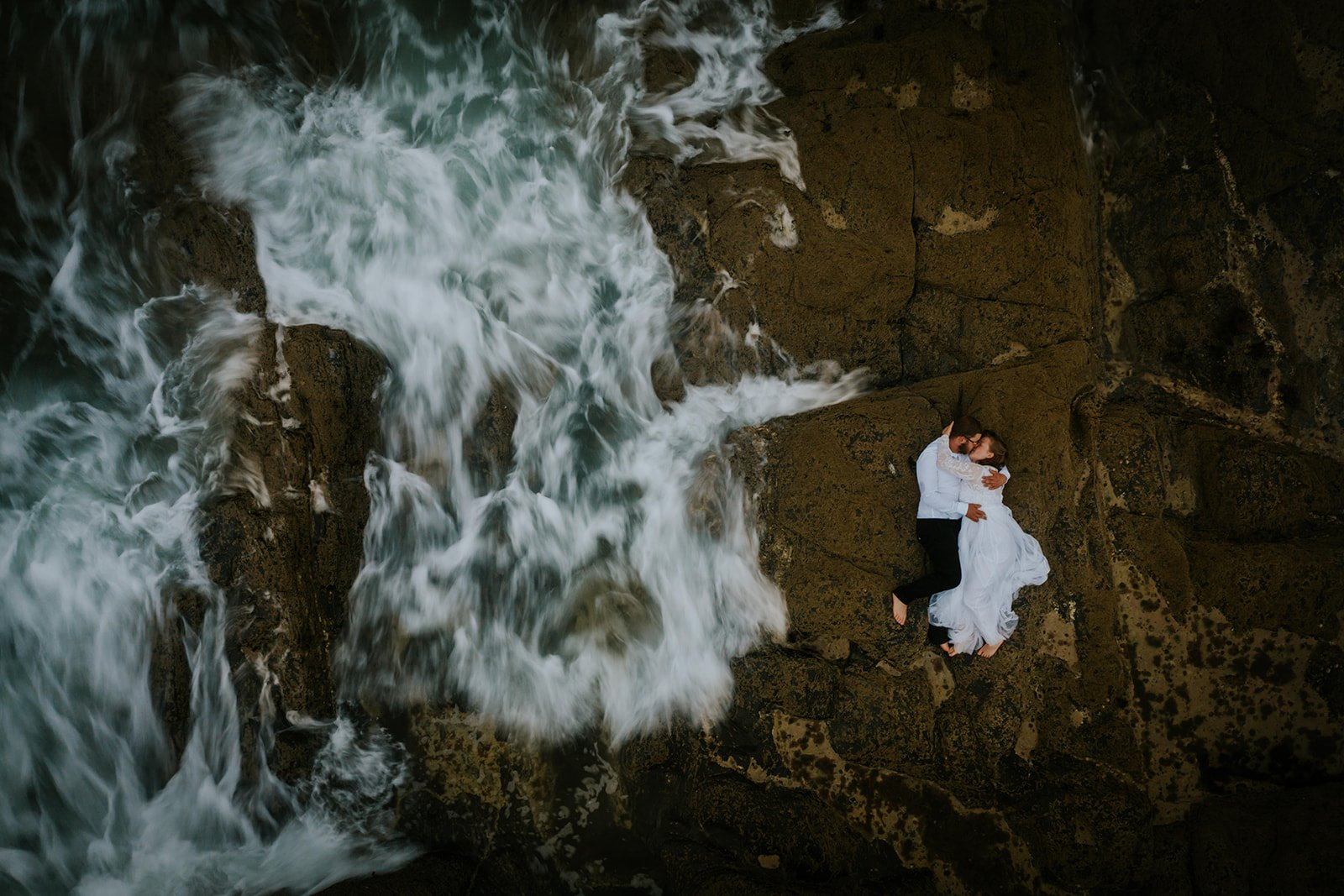 Drone Photography in Cornwall of a couple kissing on the rocks as the waves crash around them