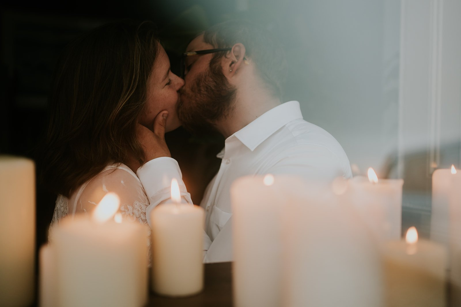 Bride and groom kiss in the window surrounded by candles during their romantic ceremony