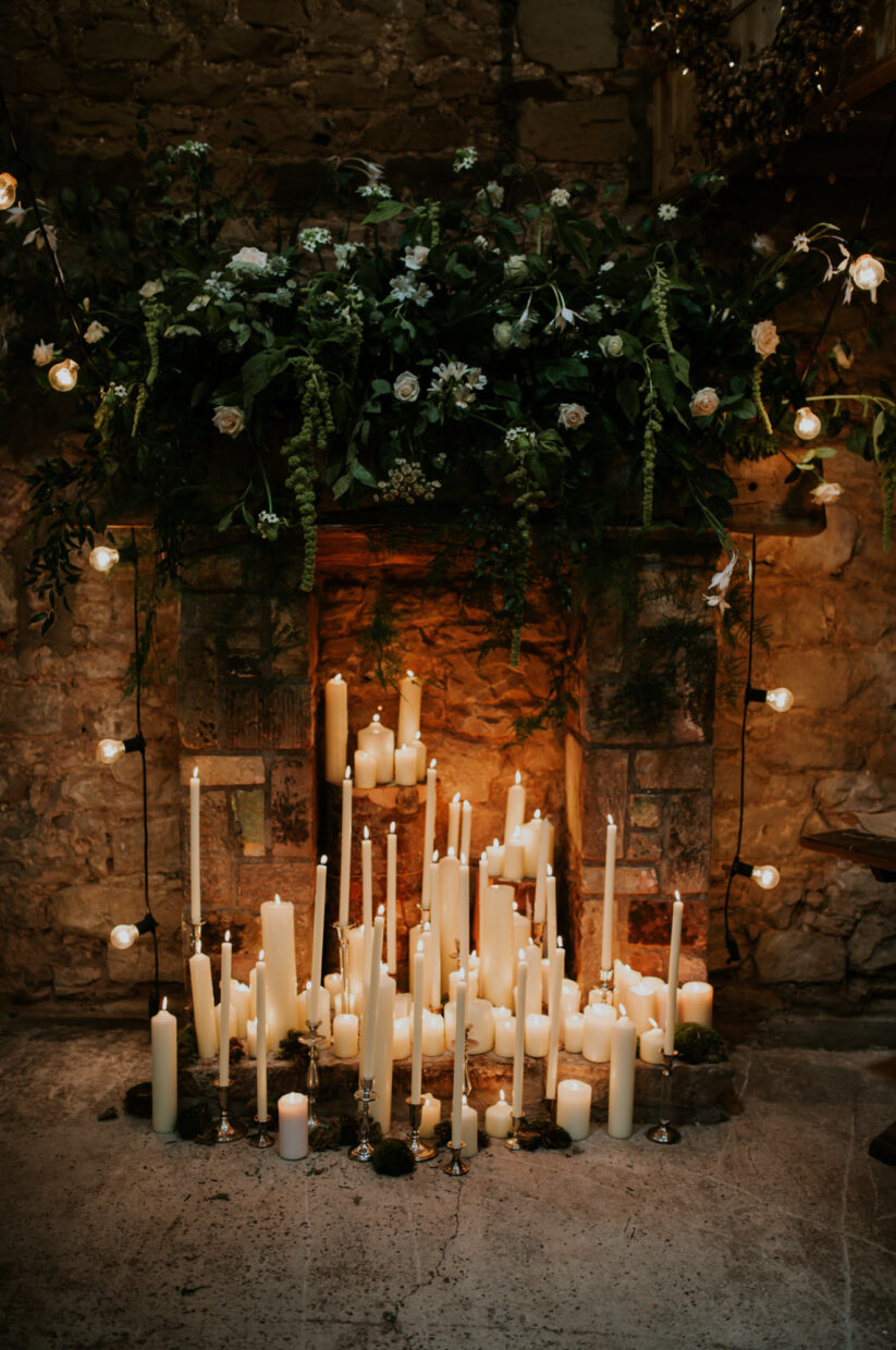 A beautiful background for a wedding ceremony filled with hundreds of candles and a big wild green foliage hanging on a big fireplace