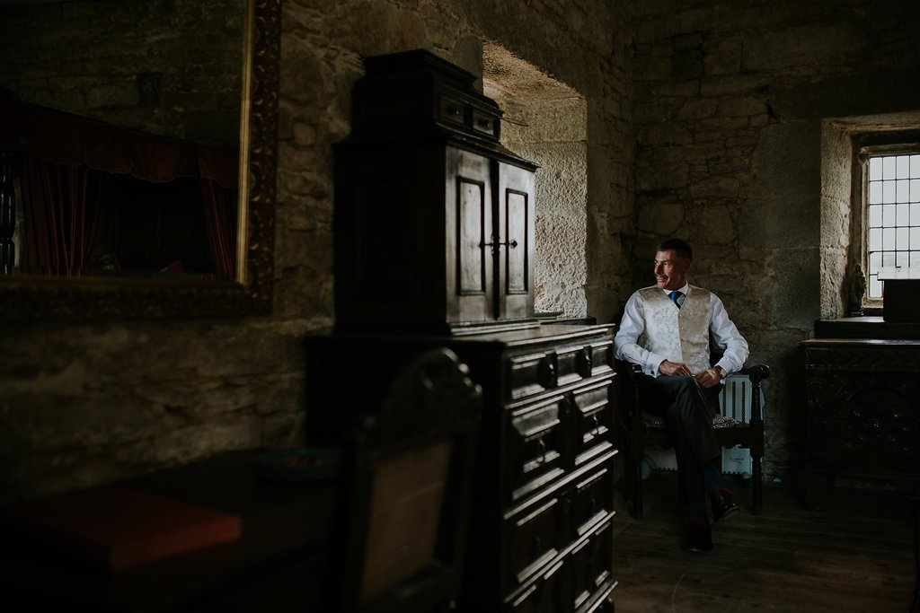 Groomafter his Getting Ready on his wedding day with window light on a castle