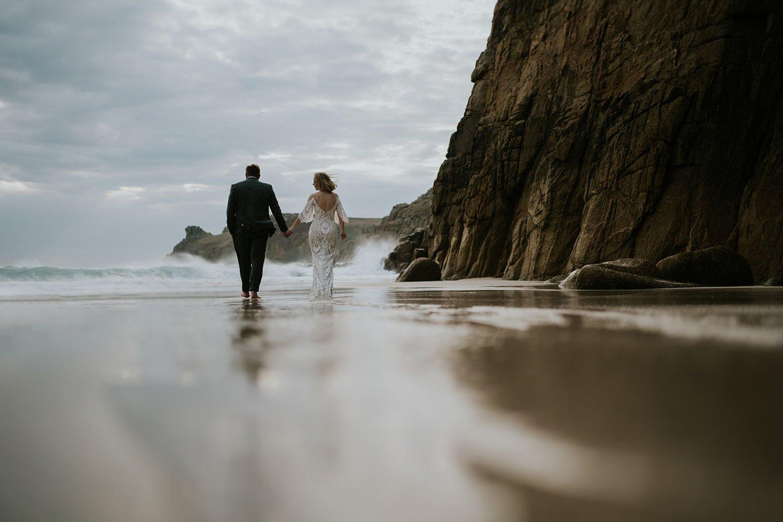 Wedding Couple walk on their boho Wedding in Cornwall on a sandy beach