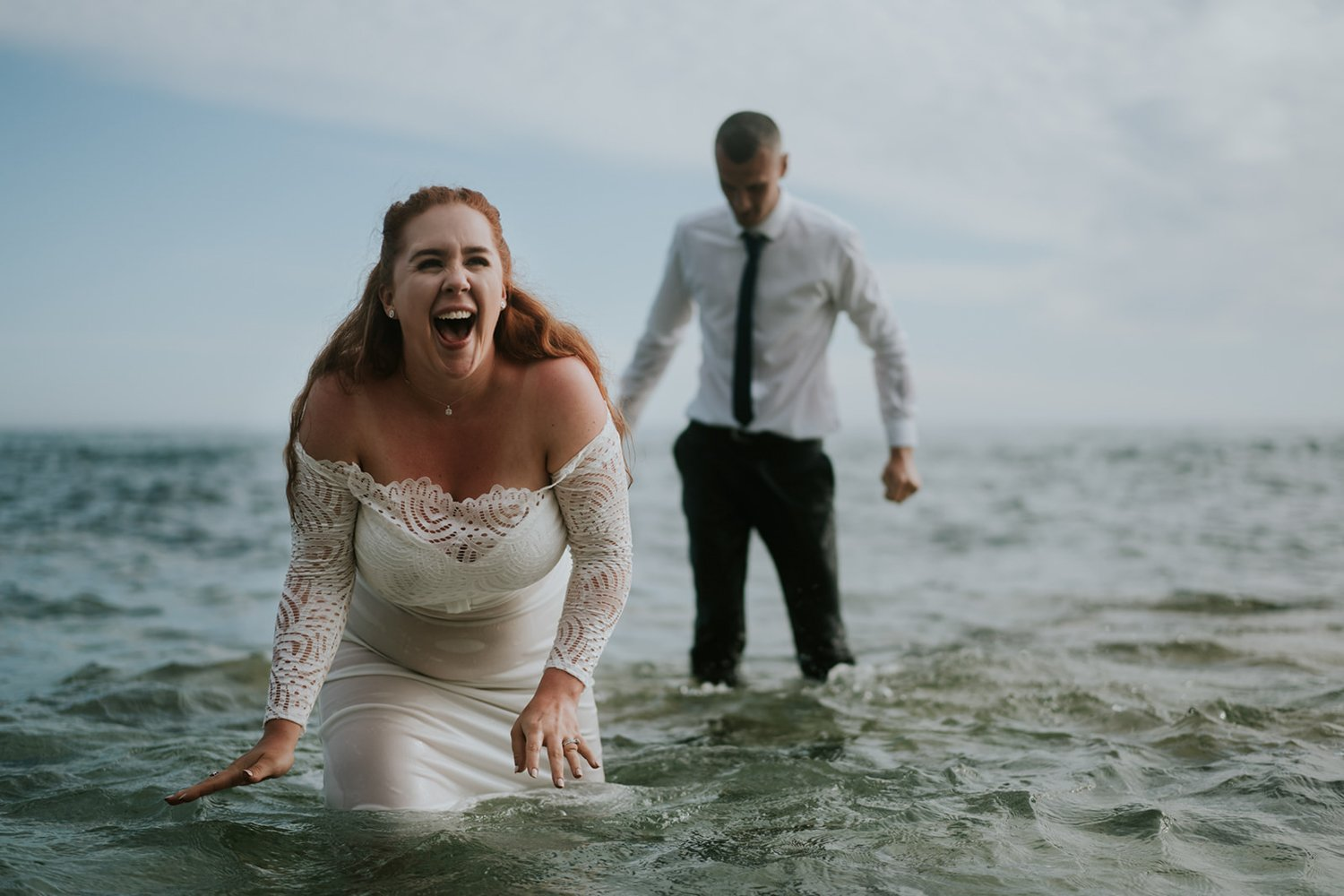 Happy Cornwall Wedding Couple kiss in the sea and have fun